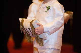 ring-bearer-in-white-outfit-holding-ring-pillow-with-monogram-embroidery-and-fringe-on-both-sides