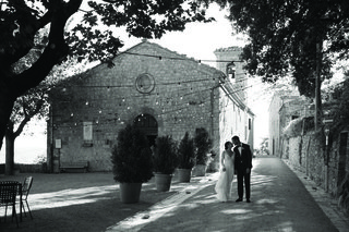 black-and-white-photo-of-a-bride-and-groom-walking-through-tuscany