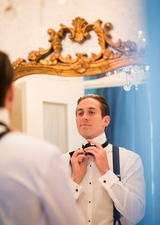 groom-prepares-for-his-ceremony-by-tying-his-bow-tie-in-the-mirror