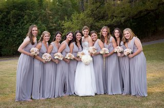 bride-holding-white-flowers-with-bridesmaids