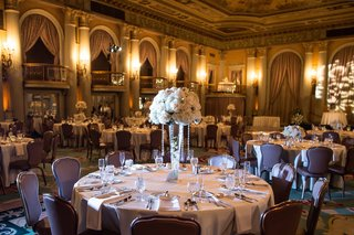 wedding-reception-table-with-tall-centerpiece-topped-with-white-flowers-and-suspended-crystals