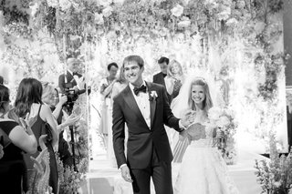 black-and-white-photo-of-black-tie-wedding-bride-and-groom-holding-hands-leaving-ceremony-space
