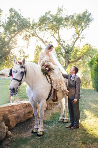 bride-in-a-claire-pettibone-dress-with-gold-and-silver-embroidery-sits-on-white-horse-groom