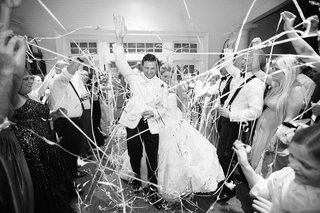black-and-white-photo-of-bride-and-groom-leaving-wedding-through-tunnel-of-friends-with-confetti