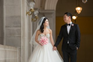 bride-in-kenneth-pool-ball-gown-and-groom-in-tuxedo-holding-hands
