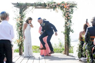 wedding-ceremony-rustic-chic-bride-in-lace-dress-with-groom-in-navy-suit-wood-arbor-flowers-greenery
