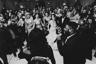 black-and-white-photo-of-live-band-singing-and-performing-at-wedding-reception-guests-on-dance-floor