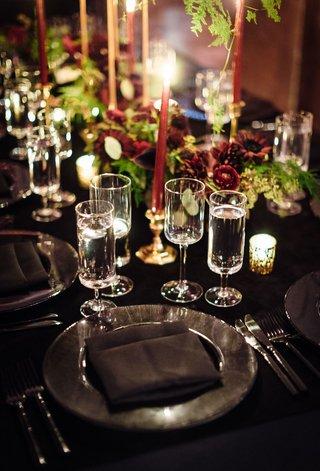 black-linen-tablecloth-black-charger-plate-black-napkin-crystal-glassware-gold-candleholder-greenery