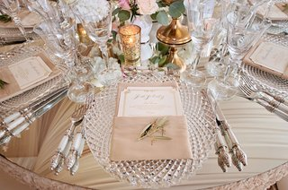 mirror-table-cut-crystal-charger-plate-menu-in-napkin-gold-candle-votives-and-white-silver-flatware