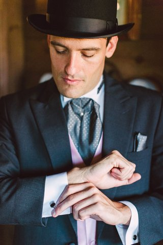 groom-in-ascot-pink-vest-pocket-square-top-hat-and-cuff-links-getting-ready-for-wedding