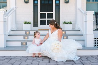 bride-in-striped-hayley-paige-wedding-dress-sitting-with-young-flower-girl