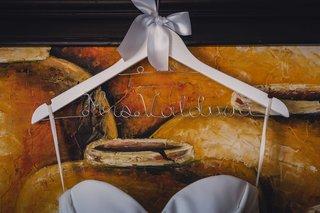 a-hanger-holding-the-brides-white-wedding-dress-that-reads-mrs-valdivia