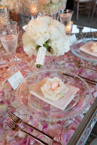 wedding-reception-place-setting-rose-on-top-of-clear-table-with-layer-of-rose-petals-pink