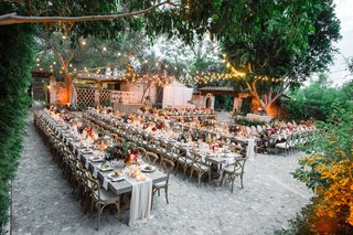 bistro-lights-draped-between-trees-long-kings-table-with-vineyard-chairs-fall-wedding