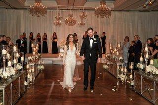 bride-in-inbal-dror-wedding-dress-holding-grooms-hand-tuxedo-mirror-ceremony-decor-chandeliers