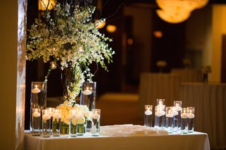 wedding-reception-with-place-card-table-decorated-with-white-orchids-and-roses-and-floating-candles