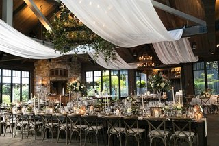 wedding-reception-white-drapery-through-rafters-beams-iron-chandelier-with-greenery-long-table
