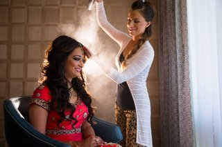 hair-stylist-sprays-hairspray-on-indian-brides-curled-wedding-hairstyle