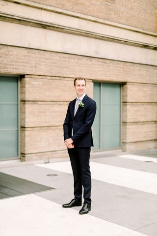 groom-in-navy-suit-and-black-dress-shoes-waiting-for-bride-before-first-look