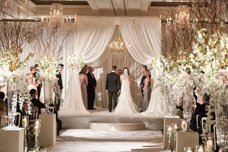 bride-and-groom-under-white-drapery-chuppah-at-indoor-chicago-wedding-with-rustic-flower-arrangement