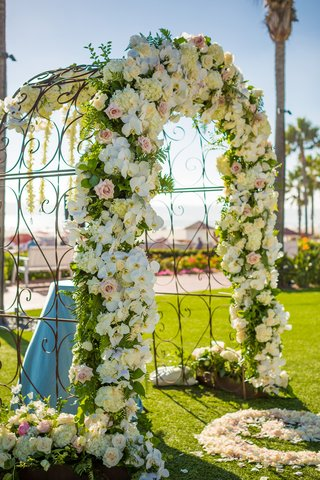 wrought-iron-arch-facade-florals-orchids-roses-beach-grass-lawn-hotel-del-coronado