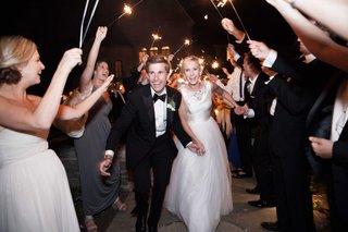 a-bride-and-groom-make-their-grand-exit-from-their-reception-while-guests-wave-sparklers