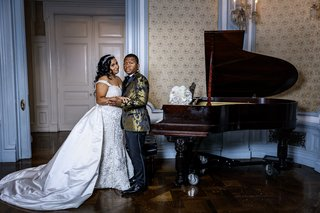 bride-in-stephen-yearick-and-groom-in-gold-and-black-jacket-pose-by-grand-piano