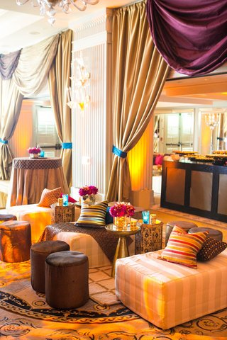 moroccan-themed-engagement-party-with-ivory-gold-striped-seating-colorful-striped-throw-pillows