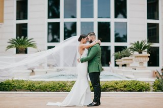 bride-in-crepe-low-back-wedding-dress-cathedral-veil-groom-in-green-tuxedo-jacket-miami-wedding