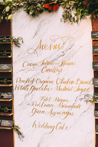 fall-theme-wedding-reception-marble-background-gold-calligraphy-menu-with-marsala-wall-greenery