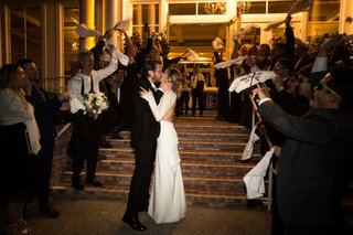 bride-and-groom-kiss-at-grand-exit-while-guests-wave-rally-rags-baseball-details-at-wedding