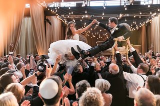jewish-hora-chair-dance-with-strings-of-bistro-lights-overhead