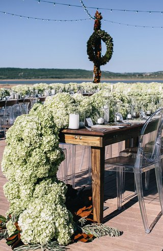 wedding-reception-in-texas-with-rustic-wood-table-and-lush-hydrangea-flower-runner-with-magnolia
