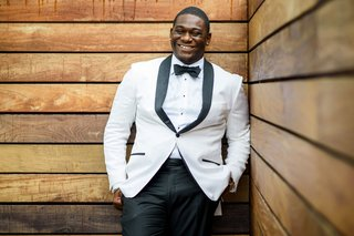 african-american-groom-in-white-tuxedo-jacket-with-black-lapels-and-black-bow-tie-slacks-pants