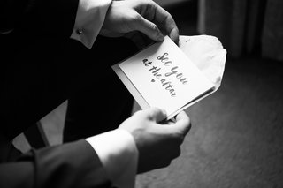 black-and-white-photo-of-groom-holding-note-from-bride-before-the-ceremony