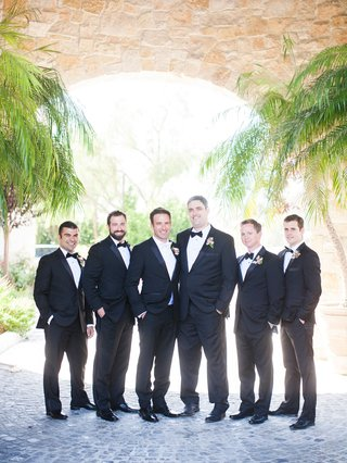 groom-in-tuxedo-with-white-bow-tie-and-groomsmen-in-black-suits-with-black-bow-ties