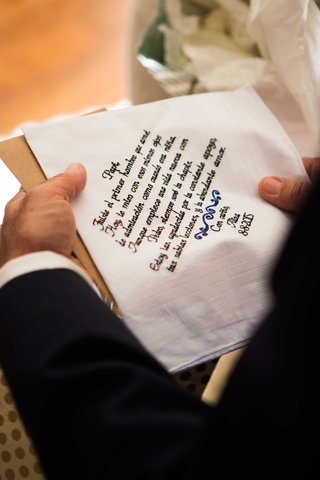 bride-gives-father-of-bride-a-handkerchief-with-notes-in-black-calligraphy-signing-it-with-her-name