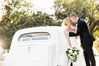 wedding-photo-of-bride-and-groom-in-front-of-classic-car-with-just-married-banner-in-back-window
