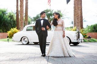couple-walking-arm-in-arm-classic-tuxedo-changes-white-dress-rolls-royce-wedding-california