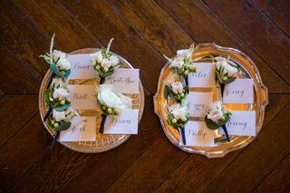 wedding-boutonniere-on-silver-tray-with-name-tags-white-rose-and-berries-greenery