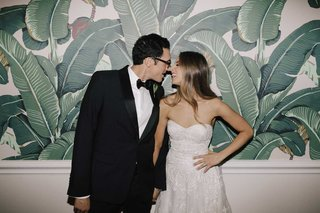 bride-in-strapless-wedding-dress-long-hair-groom-in-tuxedo-bow-tie-glasses-beverly-hills-hotel-palm