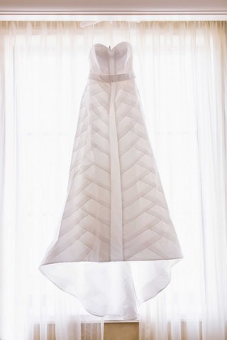 anne-barge-strapless-wedding-dress-hanging-in-sunlit-bridal-suite-room