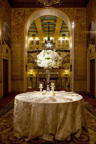 escort-card-table-with-luxurious-linens-and-large-floral-centerpiece-on-glass-vase