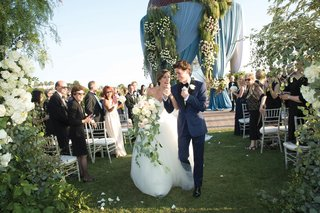 bride-in-vera-wang-ball-gown-with-cascading-bouquet-and-groom-in-navy-tuxedo-during-recessional