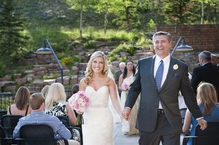 bride-and-groom-hold-hands-as-they-walk-up-aisle-as-husband-and-wife-in-outdoor-ceremony