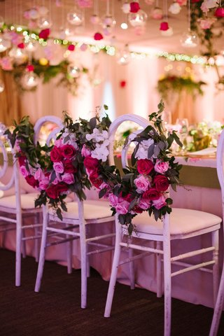 bride-and-groom-chairs-at-head-table-with-greenery-garland-pink-red-white-flowers