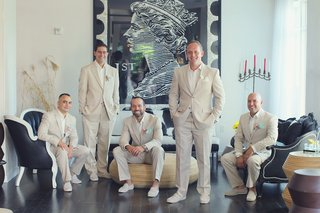 groom-and-groomsmen-wearing-light-tan-suits-in-room-with-black-furnishings