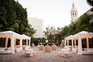 courtyard-outdoor-cocktail-hour-with-white-cabana-green-hedge-bar-and-cocktail-tables