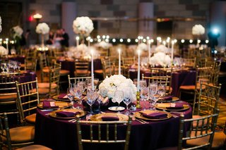 round-wedding-reception-table-with-purple-linen-gold-plates-tall-candles-and-white-flowers
