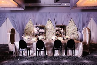 wedding-reception-with-long-head-table-in-silver-tablecloth-black-ghost-chairs-floral-panels